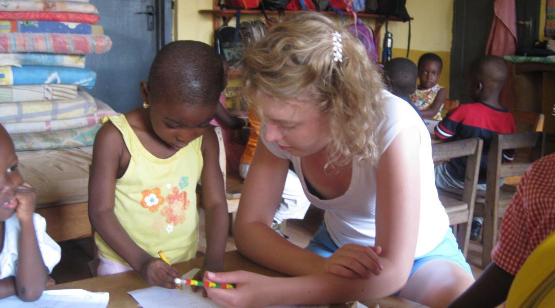 Voluntaria ayudando a una estudiante durante su voluntariado con niños en Ghana.
